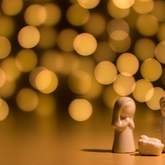 A wooden nativity with out of focus lights in the background