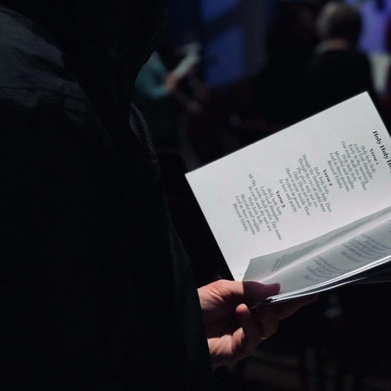A man holding a booklet with song lyrics written in it