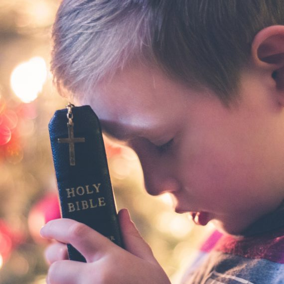A small boy praying while holding a Bible to his forehead